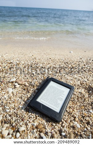 e-book reader on a beach with LOREM IPSUM text and sea i back - stock photo