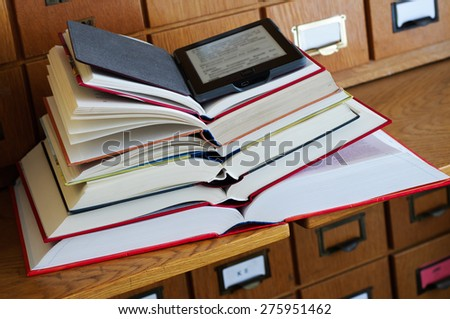 E-book Reader on top of Stack of Books in a Library - stock photo