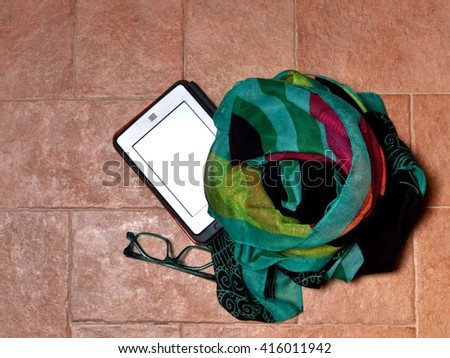 e-book reader with green eyeglasses and colored scarf on brown floor - stock photo