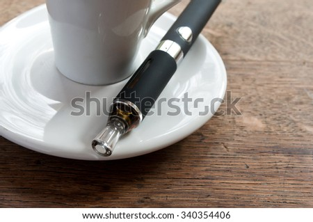 e-cigarette and cup of coffee on wooden background  - stock photo
