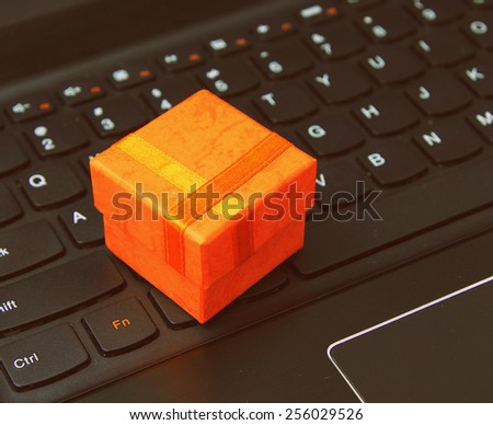 e-commerce and web shopping: orange present case on the laptop keyboard - classic style - stock photo