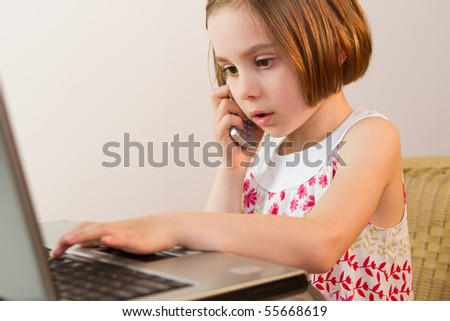 E-lerning with computer and  talking on the mobile phone - stock photo