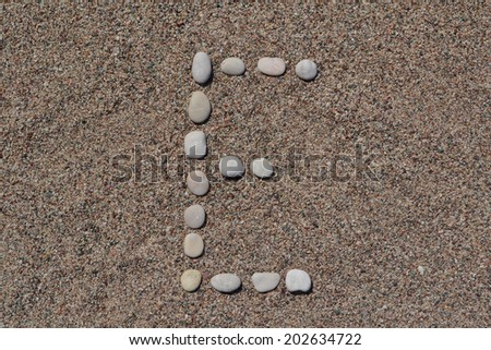 E letter made of stones on sand  - stock photo