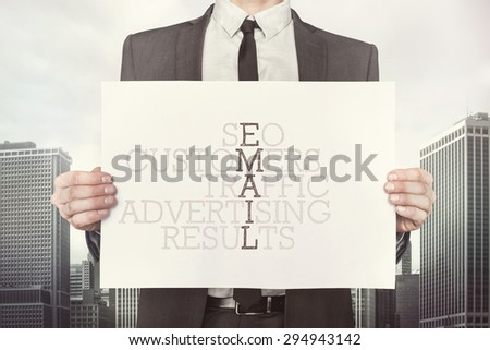 E-mail crossword concept on paper what businessman is holding on cityscape background