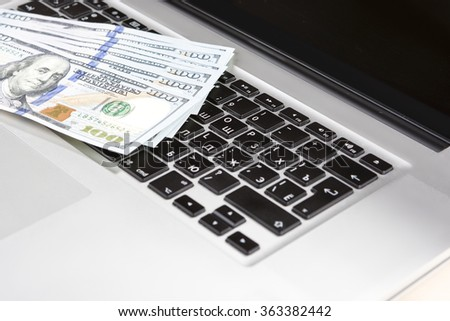 E-Trade and E-Commerce Ideas and Concepts. Stack of Banknotes on Laptop in Front of Open Screen.Horizontal Image - stock photo