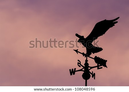 Eagle weather vane in a beautiful sky - stock photo