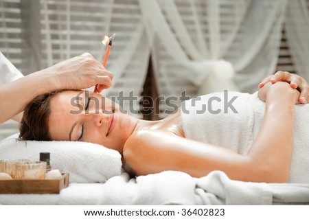 Ear candling being carried out on an attractive caucasian woman in a spa - stock photo