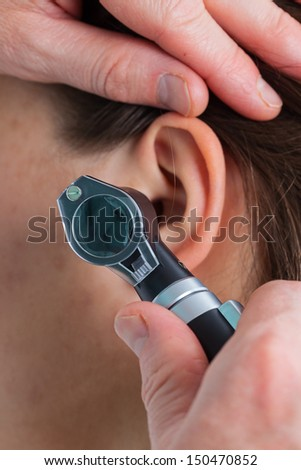 Ear examining with an otoscope, close up - stock photo