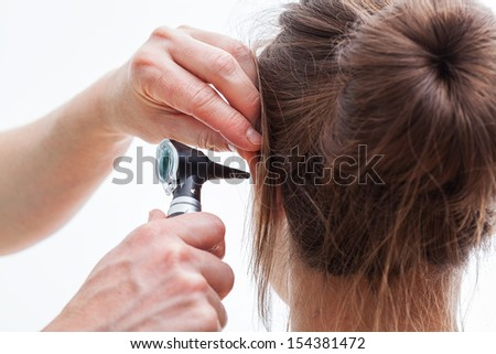 Ear examining with an otoscope, isolated background - stock photo