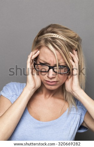 ear or headache suffering concept - beautiful young blond woman with eyeglasses having migraine,feeling dizzy or stressed by noise and tinnitus - stock photo