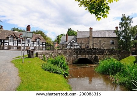 Eardisland, United Kingdom - June 5, 2014 - Stream with stone bridge and pretty cottages to the rear, Eardisland, Herefordshire, England, UK, Western Europe, June 5, 2014.