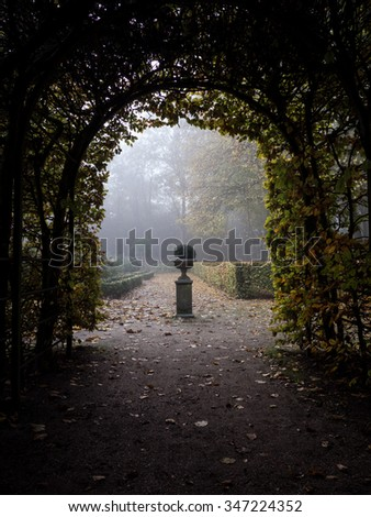 Early autumn morning in the park - archway and garden ornament - stock photo