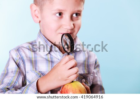 Early education nature and biology discovery. Little boy examine fruit apple with magnifying glass. - stock photo