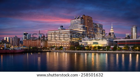 Early evening view and city lights of West Chelsea and Midtown Manhattan skyline from Hudson River. New York City - stock photo