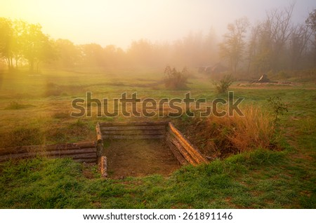 Early misty morning with sun rays. In the foreground, trenches and gun of World War II - stock photo