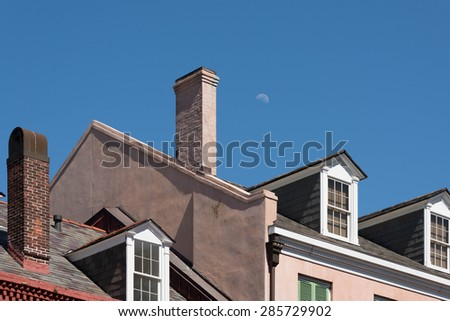Early moon makes an appearance above chimney and roofs of typical suburban town. - stock photo
