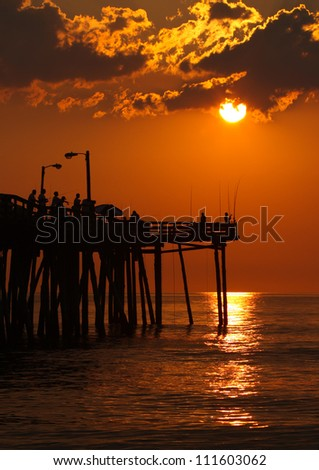 Early-morning anglers are silhouetted against the rising sun on a fishing pier in Nags Head, North Carolina vertical - stock photo