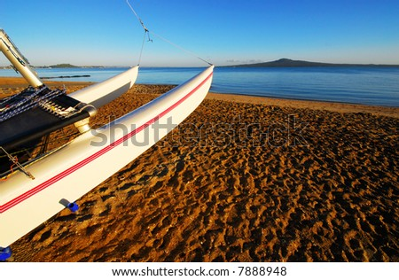 Early morning beach scene with sailboat in foreground - stock photo