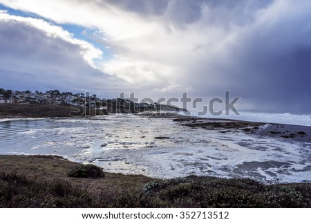 Early morning El Nino weather storm floods Central California Coast beach, with powerful wind, rain, waves, & heavy surf, near Cambria, CA. on the Big Sur Coast. - stock photo