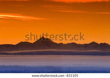 Early morning fog in the valley and skyline of the Alaska Range in Sunset
