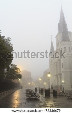 Early morning fog on Jackson square obscures St. Louis Cathedral in New Orleans, Louisiana - stock photo