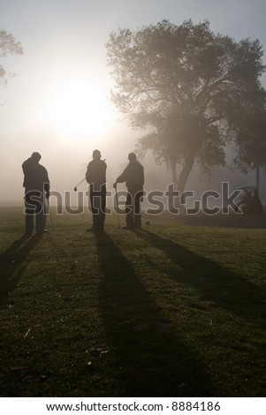 Early morning golfers silhouetted in a dense fog with a rising sun - stock photo