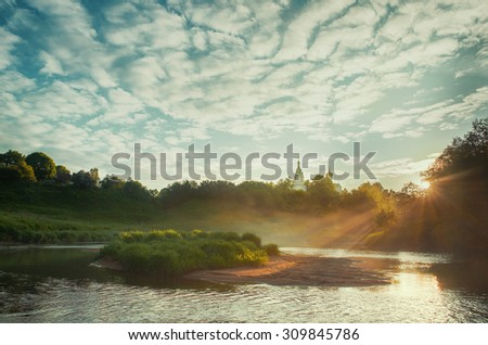 Early morning in small russian village with orthodox church at the hilltop - stock photo