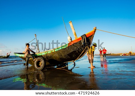 Early morning in the Hai Ly Beach, Vietnam - August 7, 2016: Fishermen are pulling their boats up on the beach. There is no jetty for mooring, so after each voyage, they pulled their boats ashore.