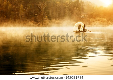 Early morning lake and the two fishermen - stock photo