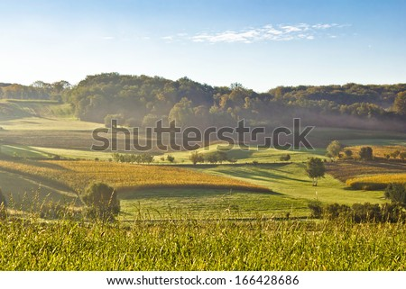 Early morning landscape in fog, idyllic fields and hills - stock photo