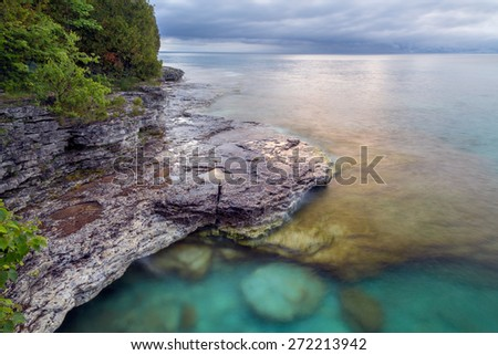 Early morning light shines down on the rocky Lake Michigan coast of Door County Wisconsin's Cave Point. - stock photo