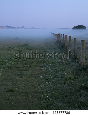 Early morning mists shrouding a field and boundary fence, at Hengistbury Head nature reserve, Dorset, England, UK - stock photo