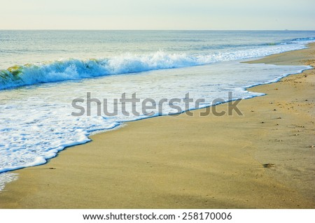 Early morning on Sandy Hook Beach, New Jersey, USA. Scenic view over Atlantic ocean,  sky, horizon, running waves over the shore. Instagram filtered look. - stock photo