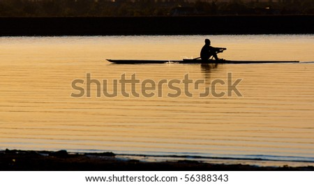 Early morning rowing on calm lake