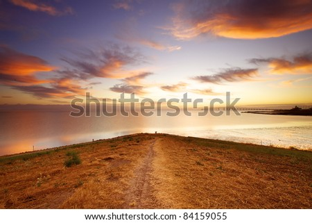 early morning sky a lot color,with a with a trail going down a sloping hillside with a water reflection, - stock photo