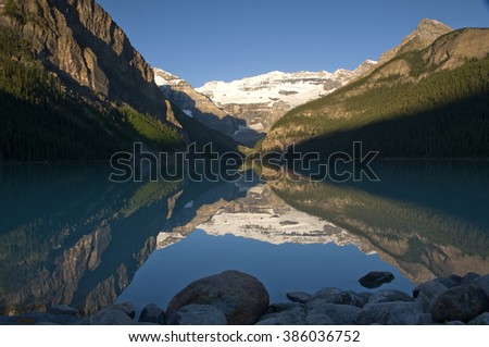 Early morning sun reflects the Plain of Six Glaciers and surrounding hills on a perfectly still Lake Louise in Banff National Park, Alberta, Canada. - stock photo