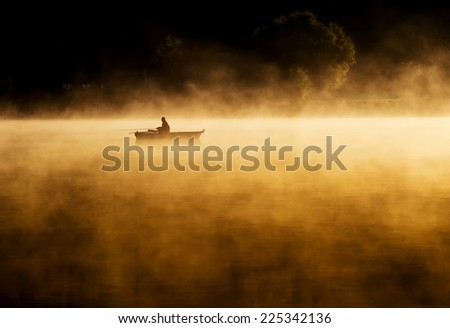 Early morning sunrise, boating on the lake in a huge fog - stock photo