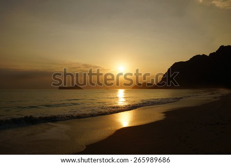 Early Morning Sunrise on Waimanalo Beach on Oahu, Hawaii over Rabbit and Rock Island over the clouds. - stock photo
