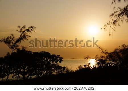 Early Morning Sunrise on Waimanalo Beach on Oahu, Hawaii over Rock Island through the trees and over the clouds. - stock photo
