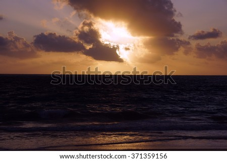 Early Morning Sunrise on Waimanalo Beach over ocean bursting through the clouds on Oahu, Hawaii and waves lapping. - stock photo