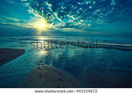 Early morning, sunrise over beach. River delta on the sea shore - stock photo