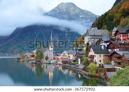 Early morning view of Hallstatt, a charming lakeside village in Salzkammergut region of Austria, with reflections on smooth lake water in colorful autumn season ~ A beautiful UNESCO heritage site