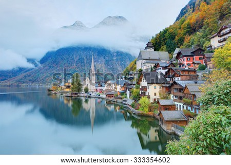 Early morning view of Hallstatt with beautiful reflections on smooth lake water, a charming lakeside village in Salzkammergut region of Austria, in the colorful autumn season
