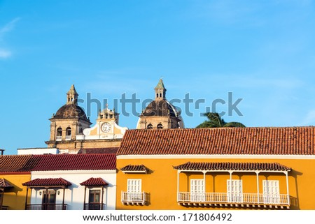 Early morning view of the facades of historic colonial buildings with a church behind them in the center of Cartagena, Colombia - stock photo