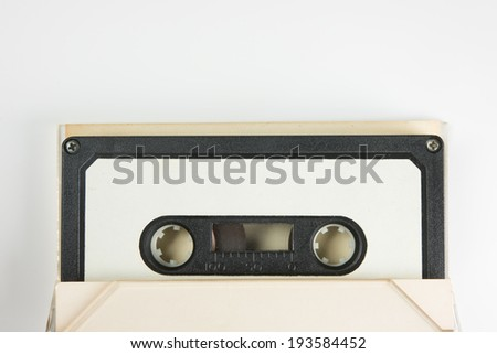 Early 70's cassette tape in sticking out from an open cassette case, on natural white background. - stock photo