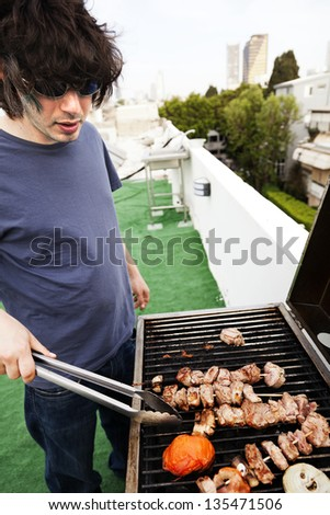 Early 30's caucasian man busy grilling some meat and vegetables on the roof of a building in urban surroundings. - stock photo