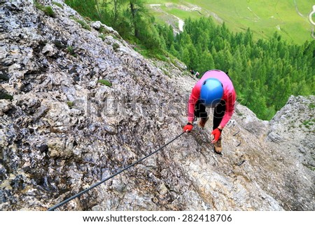 """Early section of via ferrata """"Brigata Tridentina"""" with woman climbing above lower trees and meadows, Sella massif, Dolomite Alps, Italy - stock photo"""