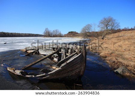 Early spring in the forest. The North of Russia, lake Onega, old boat