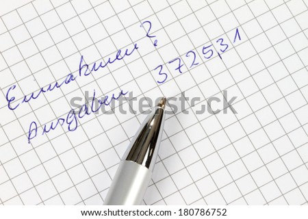 Earnings and outgoings are written in german on a checked paper decorated with a pen. - stock photo