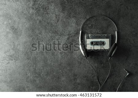 Earphone and Old cassette tape on dark background in vintage color style